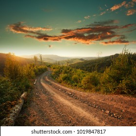 Dirt road in the mountains at sunset dramatic sky background