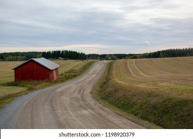 Dirt road on the countryside next to a red barn. Cloudy day in Finland