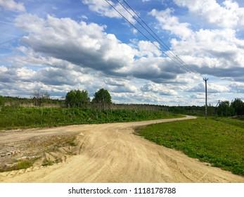 dirt road on rural outside. There are cumulus clouds in Korpisalo, Leningradskaya oblast
