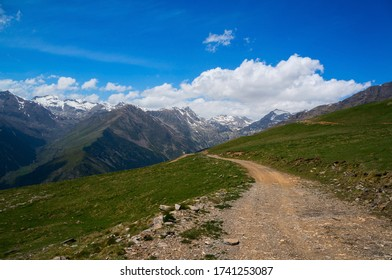 The dirt road passes through green Alpine meadows in the highlands.  Mountain Biking on the national cycle route in the Pyrenees.