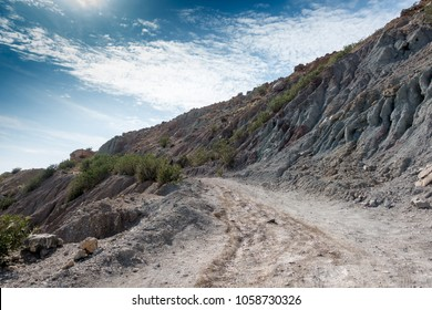 Dirt road and rocky mountain against sky, Crete, Greece