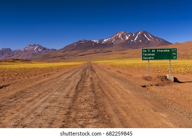 Dirt road with a road sign and mountains in the background, in the Atacama Desert, Chile; Concept for travel in Chile