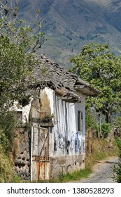 Dirt road through the countryside, lined with trees and a collapsing building in Cotacachi, Ecuador