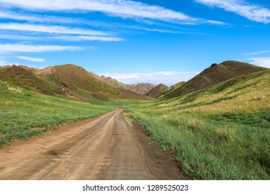 Dirt road towards the centre of Yol Valley in Gobi Desert on a beautiful summer day with blue cloudy sky (Gobi Desert, Mongolia, Asia)