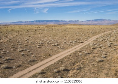 Dirt road track in the dry arid plains of central California on the border of the Mojave desert.