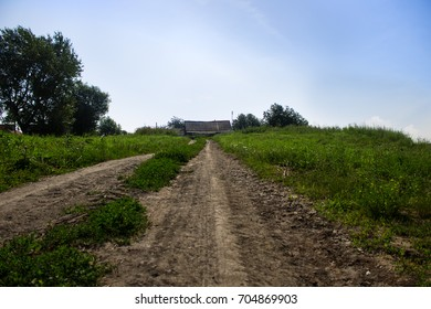 dirt road in the village. The path leads into the distance, where you can see the beautiful landscape, trees, lake and the sky. Rural dirt road in the village leads to the houses.