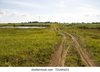 dirt road in the village. The path leads into the distance, where you can see the beautiful landscape, trees and the sky. Rural dirt road in the village leads to the mountains.