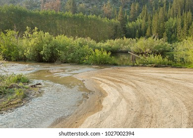 a dirt road with water flowing across it