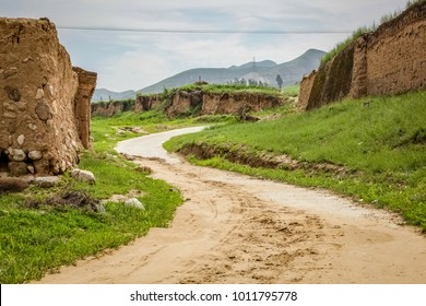 A dirt road winds up a small hill around a mud wall in rural China