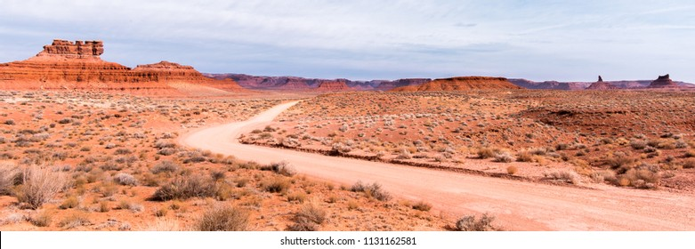 Dirt road winds through colorful rock formations and chaparral, in the Valley of the Gods, near Mexican Hat, Utah.
