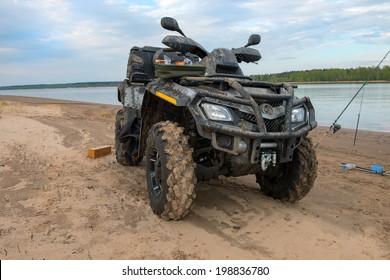 Dirty ATV stands on the banks of the river