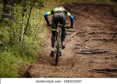 dirty back cyclist on mountainbike riding uphill in forest trail