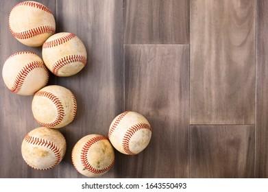 Dirty Baseball balls on a hardwood floor