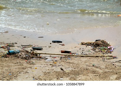 Dirty beach with pollution of tropical sea. Plastic garbage, foam, rubbish and dirty waste on beach in summer day.  Outdoors