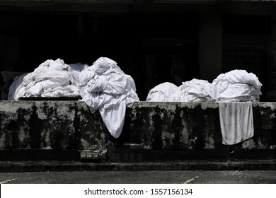 Dirty bedsheets and linens from nearby budget hotels and inns are being gathered and sorted out at the back of a commercial dry cleaning shop to be washed and cleaned.