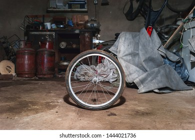 Dirty Bicycle Wheel on the Floor of a Messy Home Garage with Equipment, Workbench, Tools and Cloth in Background.