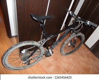 dirty black bike after a ride is in the hallway of a city apartment.