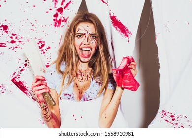 Dirty in blood, a woman holds in her hand a bloody cleaver on a white background in the studio. Young butcher girl holding a piece of raw meat and a cleaver isolated on bloody white background