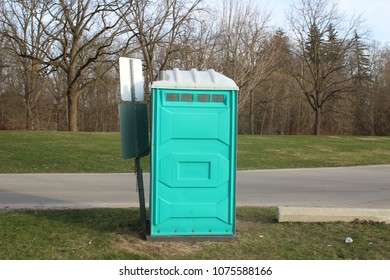 A Dirty, Blue Portable Toilet in a Park, nasty looking place to go to the bathroom