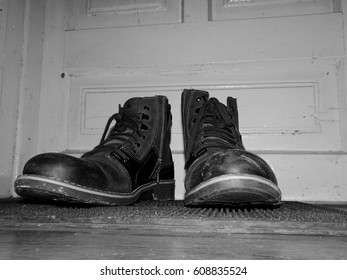 Dirty boots on old wooden door background in black and white