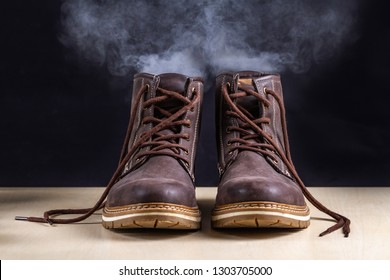 Dirty boots with an unpleasant smell. Sweaty shoes after long walks and active lifestyle. Footwear needs in cleaning and odor removal. Shoe care and shine
