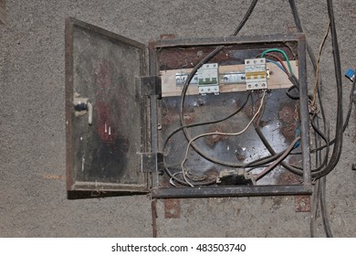 A dirty, broken and abandoned European electrical shield with wires hanging all over it.