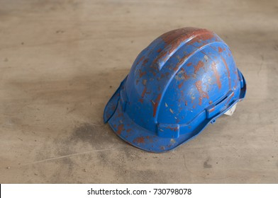 Dirty and broken blue safety helmet after paint bucket fell on head