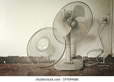 Dirty broken old electric fan in hot weather. Process in warm tone color.