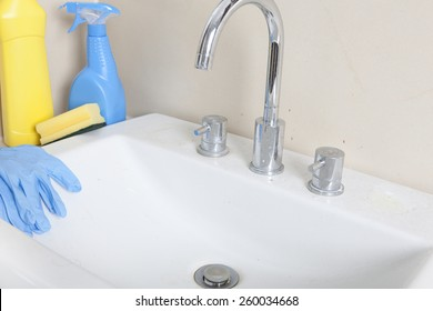 a dirty and calcified sink with cleaning gloves and cleaning products