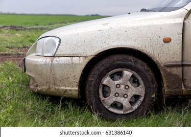 the dirty car, the car costs on a green grass in the field, the right front fender close up splodgy with dirt.