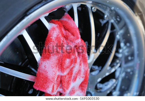 the dirty car rim is foamy cleaned with a rag