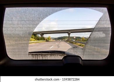 dirty car view from inside the car through the rear window, back window of a dirty car with a view of the asphalt road with markings and a road bridge.