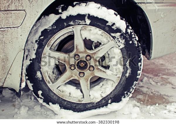 Dirty car wheel in snow