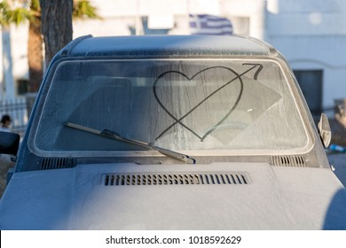 Dirty car window with drawn heart and arrow on it