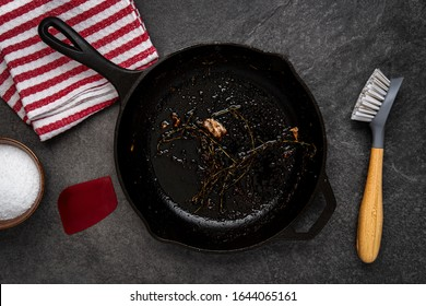 Dirty cast iron skillet being prepared for cleaning with coarse salt, brush, scraper and dish towel on a counter.