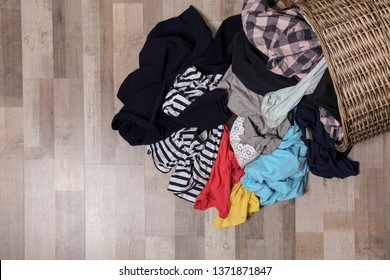 Dirty clothes scattered from laundry basket on floor, top view. Space for text