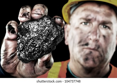 A dirty coalminer displays a lump of coal as a power and energy source.