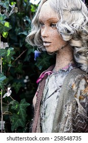 The dirty, cracked face of a beautiful mannequin amongst ivy outside.