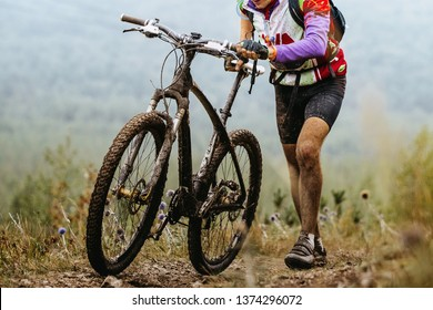 dirty cyclist climbing mountain trail with mountain bike on foot