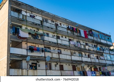 Dirty dilapidated block of flats with clothes hanging to dry on windows and balconies. Inspires poverty, indigence and misery.