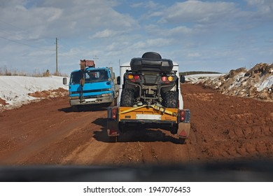 Dirty dirt road in the spring after the snow melted against a blue sky. A car with a trailer goes on the road