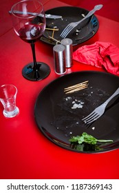 Dirty dishes after dinner on the red table. A mess after eating