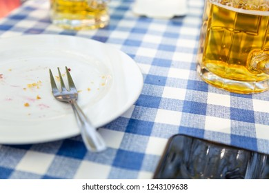 Dirty dishes after a Party is on the table with white blue tablecloth