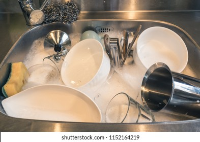 dirty dishes in the kitchen sink with water at home