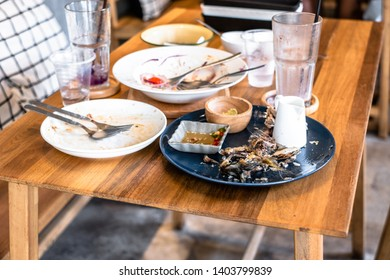 Dirty dishes of leftover food on table in restaurant.