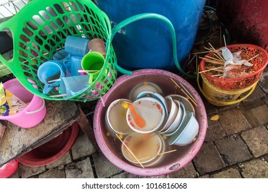 Dirty dishware inside plastic bowl, ready for cleaning. Equipment a street restaurant, Thailand.