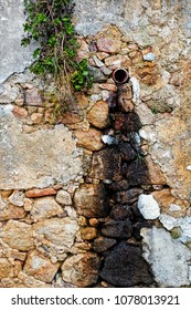 Dirty drainpipe on stone wall