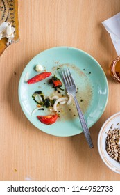 Dirty empty plate after finished food with pieces and crumbs left on its surface. Vegan dinner, vegetarian lunch, healthy food. Kitchenware concept for restaurants, cafes and kitchen.