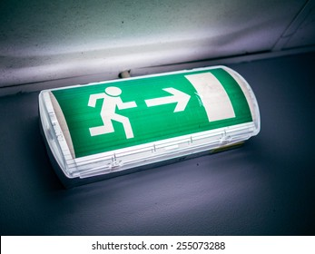 Dirty exit sign glowing in a dark room