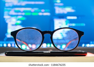 Dirty Eyeglasses in front off computer screen with Code syntax